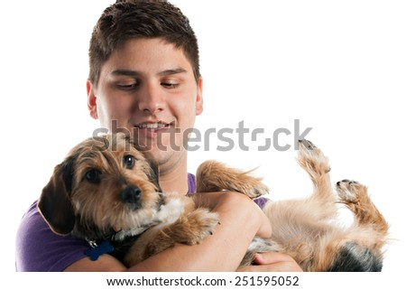 High key portrait of a young man holding a cute mixed breed dog isolated over white. Shallow depth of field with focus on the mans face. - stock photo