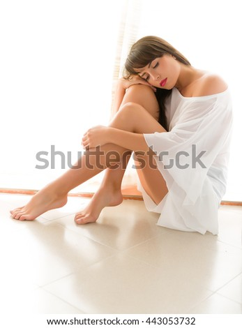 High Key portrait of a young woman sitting in front of a sunny window