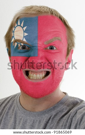 High key portrait of an angry man whose face is painted in colors of taiwan flag