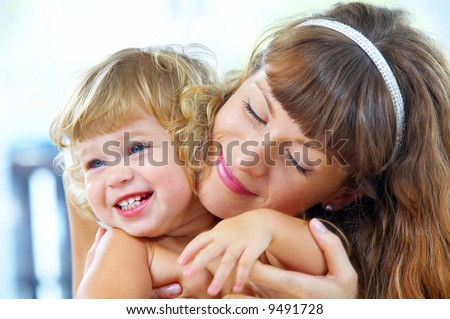High key portrait of happy mother with baby - stock photo