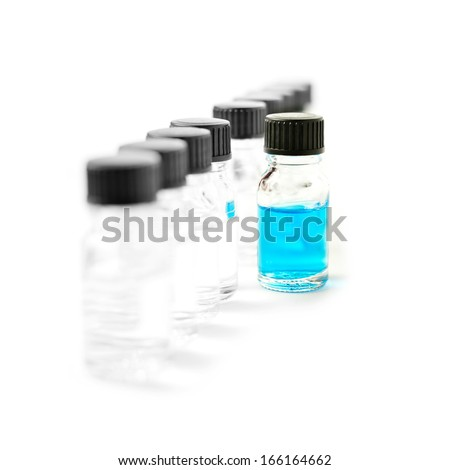 High-key studio macro of laboratory specimen bottles filled with clear liquid with one filled with blue against a white background. Copy space. - stock photo