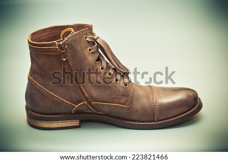 High leather boots brown. Fashionable men's autumn shoes. photo toned green - stock photo