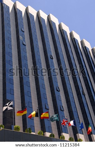 High modern corporate building with flags - stock photo