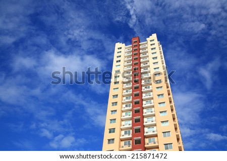 High modern stylish apartment building against blue sky - stock photo