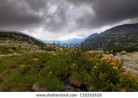High mountain scenery with rocks and dramatic storm clouds - stock photo
