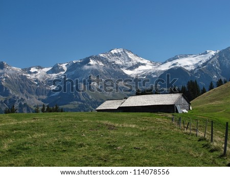 High Mountains And Old Hut With Traditional Timber Roof - stock photo