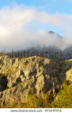 High mountains covered with greenery, in the clouds