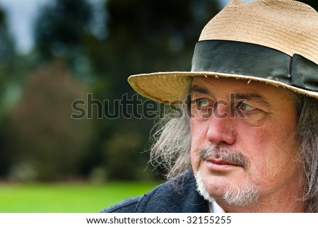 High Noon - Middle aged man with beard and mustache wearing old straw hat with 'high noon' pose and demeanor - stock photo