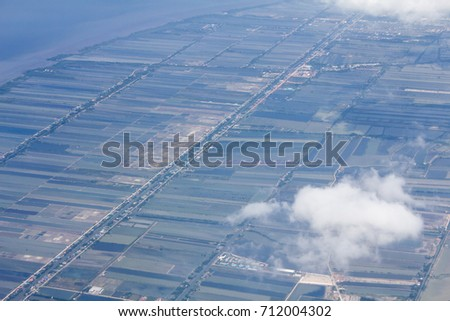 High or top view from airplane that there are agricultural area under clouds
