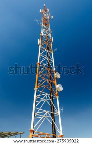 High orange and white antenna mast on blue sky background - stock photo