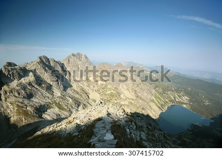 High peaks of the Tatra mountains towering over the valley. - stock photo