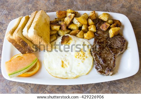 High protein breakfast plate: Sirloin stake and fried eggs. Sides dishes and garnish include potatoes, cantaloupe,  orange slice with toasts socked in melted butter. - stock photo
