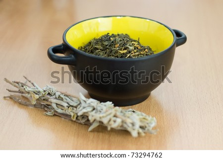High Quality Green Tea closeup in the yellow bowl with Salvia