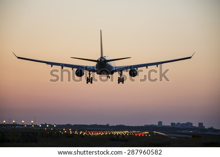 High quality picture of a plane landing before sunrise.