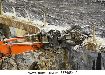 high reach demolition equipment excavator  vehicle heavy equipment  tearing down  a bridge over the freeway in  aerial view close up - stock photo