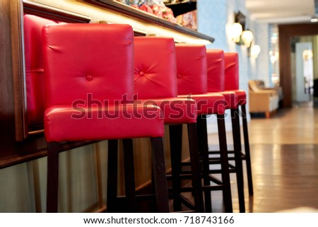 high red bar stools standing in a row in a restaurant near the bar counter