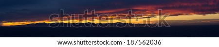 High resolution panoramic sunset over the coast of New Zealand as the sun illuminates the clouds with brilliants reds and oranges with the ocean providing foreground - stock photo