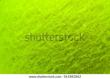 High resolution photo of a new tennis ball showing the texture of a bright green felt. The tiny treads are clearly visible although due to the curvature of the ball it is not entirely in focus. - stock photo
