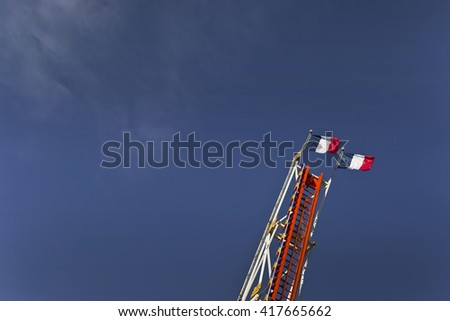 High ride and French flags in a fairground - stock photo