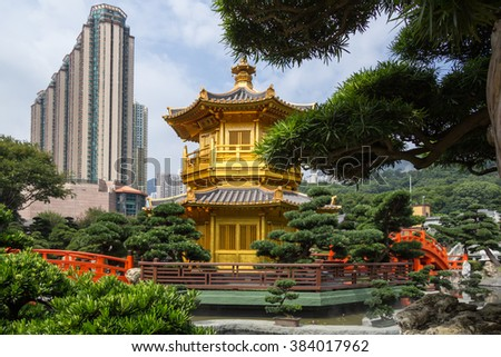 High-rise apartment buildings in the background and Golden Pagoda with red bridge in Nan Lian gardens, Kowloon City, Hong Kong - stock photo