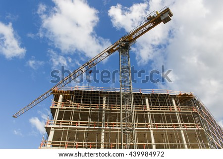 High rise building construction site with cranes against blue sky. - stock photo