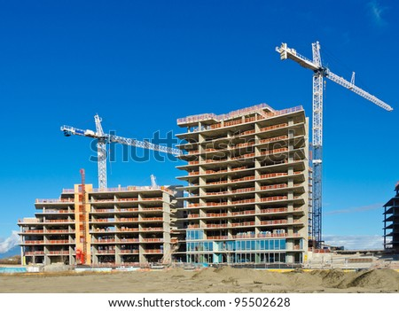 High-rise building construction site with cranes against blue sky - stock photo