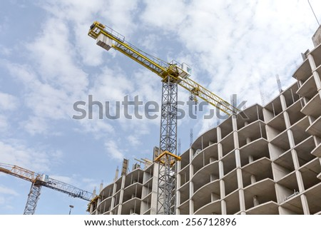 High-rise building construction site with yellow tower cranes - stock photo