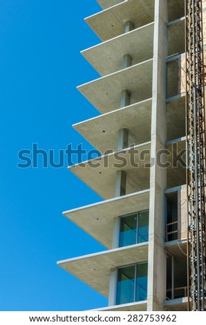 High rise building under construction. The site with cranes against blue sky. Vancouver, Canada. Vertical. - stock photo