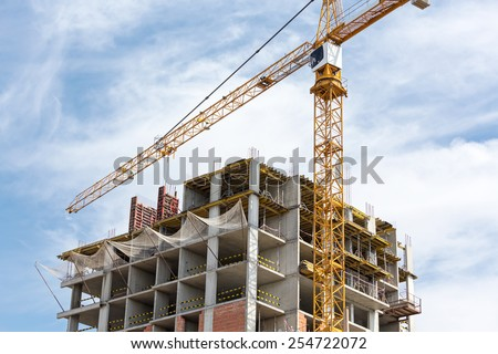 High-rise building under construction with tower crane and scaffolding - stock photo