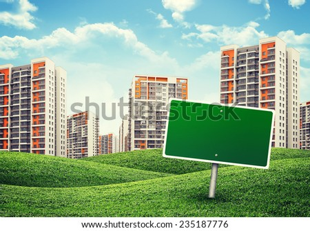 high-rise buildings of same design over green hills, blank green billboard out of upright on foreground - stock photo