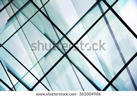 High-rise / multistory glass architecture. Multiple transparent wall, ceiling and floor panels in steel frames. Contemporary office building / modern interior design with all-over glazing. - stock photo