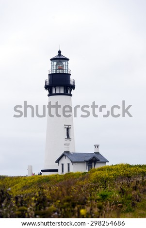High round Lighthouse illuminates correct way for ships sailing in ocean prevent shipwreck as symbol of right direction in life goals, located on high cliff on Pacific coast. Place of tourists local