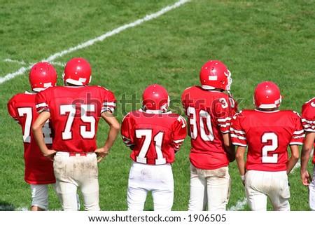 High School Football Team on Sidelines - stock photo