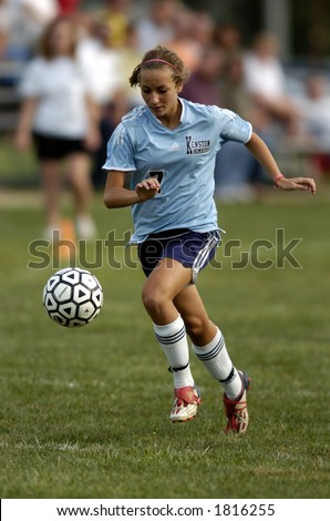 high school girl soccer player runs with eye on the soccer ball - stock photo