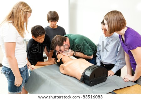 High school health class instructor demonstrates CPR lifesaving techniques for his students. - stock photo