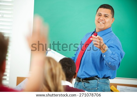 High School: Hispanic Teacher Calls on Student - stock photo