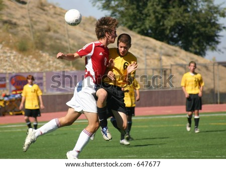 High school soccer players bring down the ball.  (Editorial use only) - stock photo