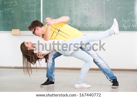 High school student in classroom surrounded with his jumping friends - stock photo