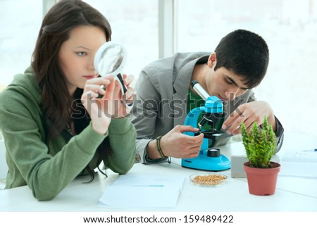 High School students concept. Group of excited students working in science classroom and discovering  biological samples with microscope and magnifying glass  - stock photo