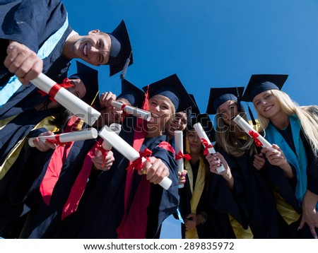 high school students graduates tossing up hats over blue sky. - stock photo