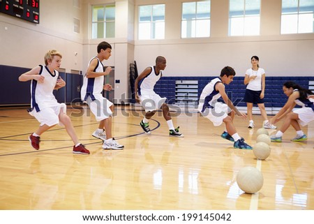 High School Students Playing Dodge Ball In Gym - stock photo
