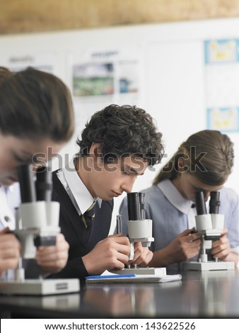 High school students using microscopes in laboratory - stock photo