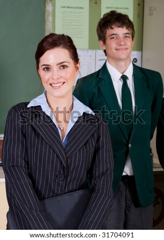 high school teacher and her student in classroom - stock photo