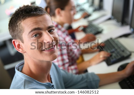 High-shool boy sitting in front of desktop computer - stock photo