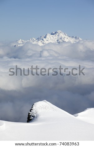 High snowy peaks over a grey cloud sea - stock photo