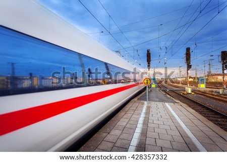 High speed passenger train on tracks in motion at sunset. Commuter train. Railway station in Nuremberg, Germany. Railroad with vintage toning - stock photo