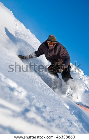 High Speed Snowboarder turning sharply in powder snow, ice crystals flying - stock photo