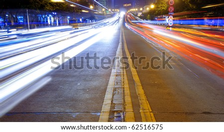 High speed traffic and blurred light trails in downtown night scene - stock photo