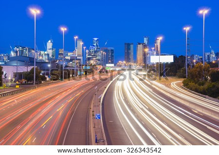 High speed traffic and light trails in highway with illuminated skyscrapers in the background at twilight - stock photo
