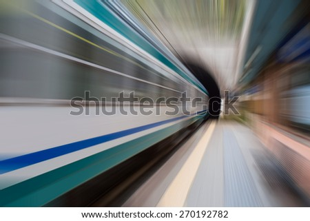 high speed Train disappearing into a tunnel - stock photo